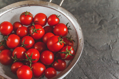 raw whole washed cherry tomatoes in a colander on a dark concrete background. View from above. Flat lay.
