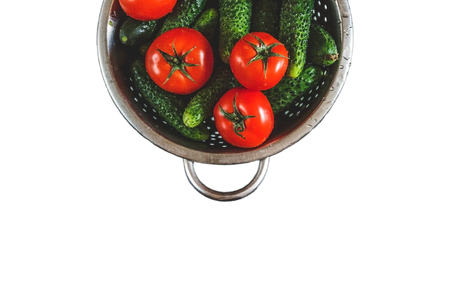 raw whole washed tomatoes and cucumbers in a colander isolated on white background. View from above. Flat lay.
