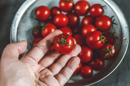 hand selects and shows whole fresh cherry tomatoes in a colander. Archivio Fotografico