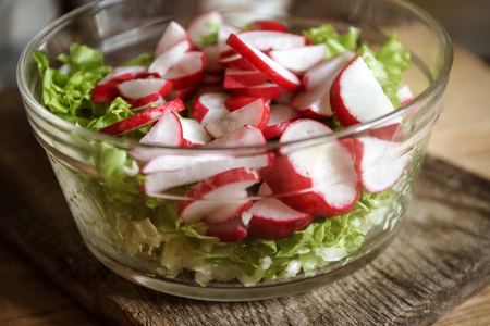 Vegetable vegan salad of wild garlic, radish, spring onions, cabbage and lettuce in a large transparent dish on an antique wooden background. Close-up, top view, flatlay. White background. The concept of healthy proper nutrition