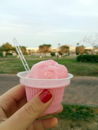 Soft pink ice cream in a plastic cup in a female hand on the background of a tropical hotel resort.
