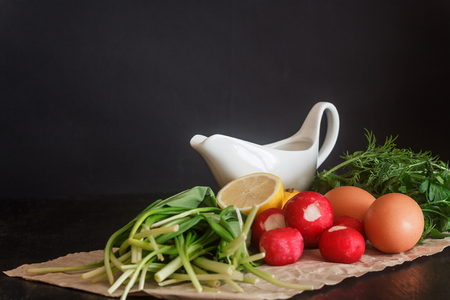 Prepared fresh vegetables and products for salad, wild garlic, radish, lemon, urkop, chicken eggs, sauce in a saucepan on parchment paper on a dark background Stock Photo