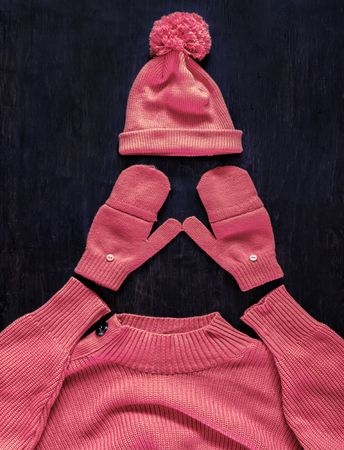 Cap with pompon, mittens, sweater in pink-red-manzhent-purple color on a dark wooden background. Top view, flat lay.Concept stylish youth warm autumn-winter. Archivio Fotografico