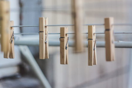 Wooden clothespins on a clothesline, blur, light photo. The concept of eco-consumption, the use of natural materials, awareness.