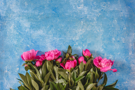 bouquet of pink-purple peonies in a vase on a blue marble-concrete background. View from above. Flat Lay.