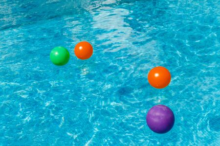 Inflatable water fun balls float on the water in the pool. Concept, cheerful, perky bright colorful summer and relaxation. View from above