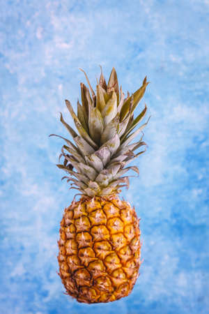 Fresh and juicy pineapple on a bright blue marble background. Close-up. Top view Фото со стока