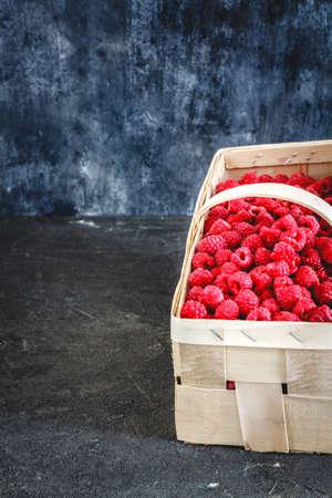 bright juicy ripe red raspberries in a basket on a dark retro background.