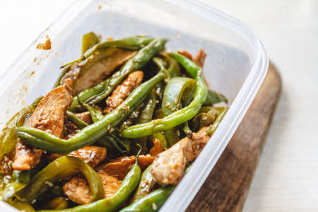 Chicken stew and green beans in plastic ovens
