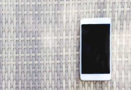White smartphone lies on a wicker outdoor table. View from above