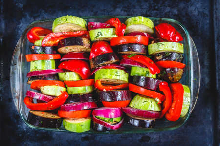 Assorted different bright and juicy baked vegetables, zucchini, eggplant, zucchini, tomato, pepper, onion on a dark retro background. The concept of healthy proper healthy vegan food. View from above