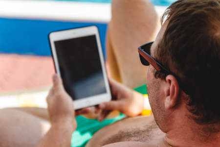 A young man in sunglasses holds a tablet in his hands. Freelancer job concept on the beach and vacation. Фото со стока