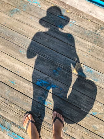 Top view, photo of bare feet and a pair of shadows on a wooden old floor. Photos on vacation, beach, summer.