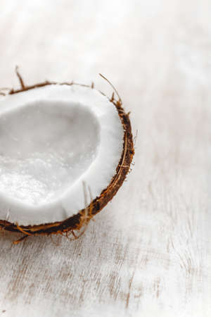 half coconut on a light white wooden background, closeup. Top view