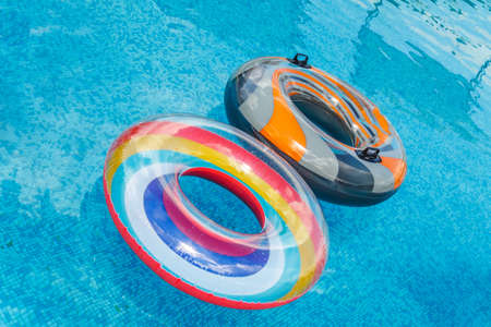 Inflatable water activities circles tuba float on the water in the pool. Concept, fun, perky summer and relaxation Фото со стока