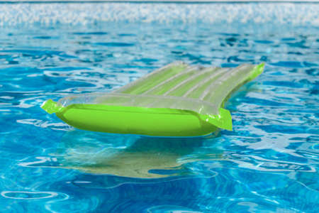 Inflatable water activities mattresses float on the water in the pool. Concept, fun, perky summer and relaxation. Top view