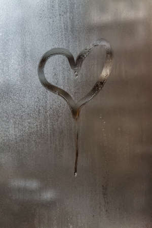 Drip in the shape of a heart on a misted window-glass. Close-up. Background.