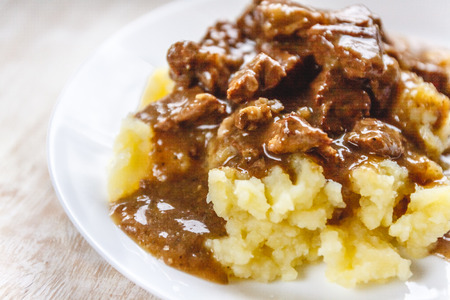 Braised beef, beef stroganoff with gravy on mashed potatoes. Close-up, top view Reklamní fotografie