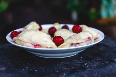Dumplings with cherries in a plate on a dark retro background Stock fotó
