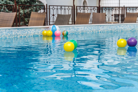 Inflatable water activities, balls, mattresses, circles, tubes float on the water in the pool