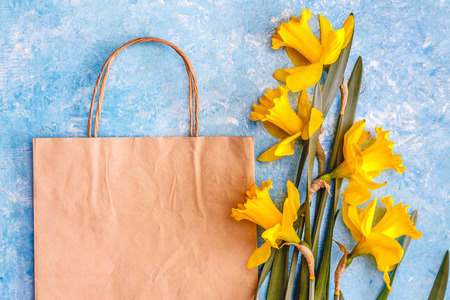 Narcissus flowers are yellow on a blue marble background and craft paper bag. Flat Lay. View from above. Concept spring ecological natural holiday shopping. 版權商用圖片