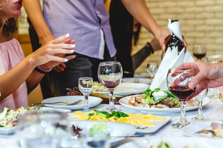 People communicate at a festive table with food and glasses in a restaurant or at a banquet. Stok Fotoğraf