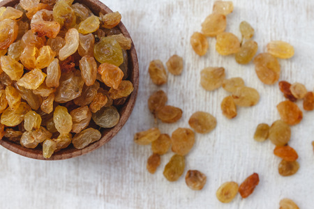 Light yellow raisins in a wooden bowl on a light white background. Close-up. Isolated