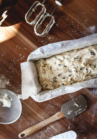 The process of making cake-bread with raisins in a metal baking dish on a dark background. Close-up. View from above. Copy space. Stock Photo