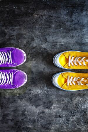 purple old worn dirty torn sneakers and and new yellow sneakers against a dark grunge background. view from above. Copy space.
