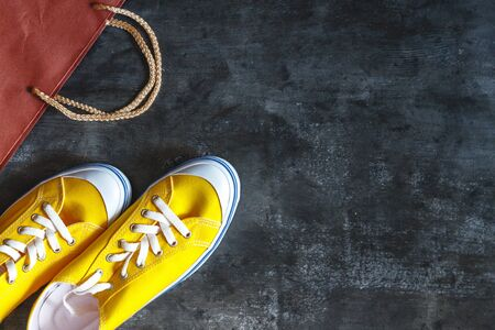 New yellow sneakers, box and package from the store on a dark concrete background. View from above. Copy space.