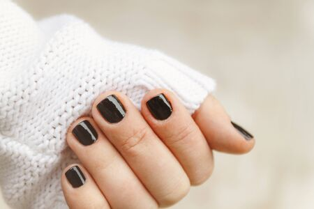 hand with black manicure on short nails in a white sweater on a light background. The concept of a stylish and warm winter. 版權商用圖片 - 132117900