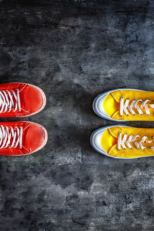 red, old, worn, dirty, torn, sneakers, and new yellow sneakers against a dark grunge background. view from above. Copy space.