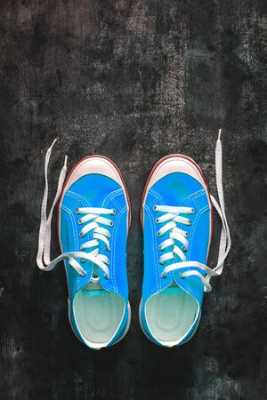 blue-cyan-green-turquoise sneakers with untied laces on a dark concrete background. Copy space. View from above