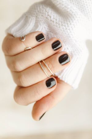 hand with black manicure and rings on the phalanges on short nails in a white sweater on a light background. The concept of a stylish and warm winter.