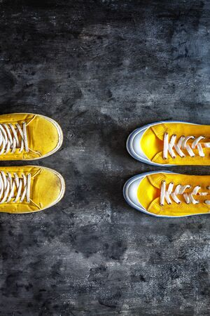 yellow old worn dirty torn sneakers and and new sneakers on a dark grunge background. top view. Copy space Stockfoto