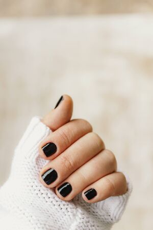 hand with black manicure on short nails in a white sweater on a light background. The concept of a stylish and warm winter.
