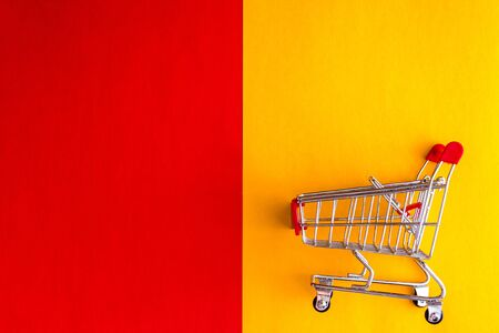 On a yellow-red background, a grocery cart-basket and a question mark. Flat lay, Top view, copy space. Concept, choice of shopping, reasonable and economical shopping.