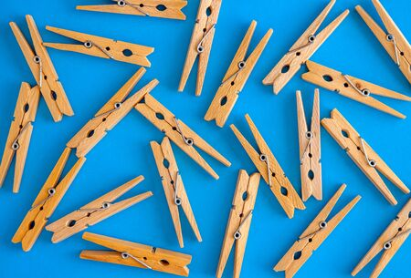Wooden yellow clothespins are scattered on a cyan-blue background. Frame of clothespins. View from above. Copy space. Flat lay. The concept is natural, eco-friendly. Archivio Fotografico