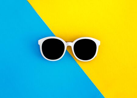 Sunny stylish white sunglasses on a bright blue-cyan and yellow-orange background, top view, isolated. Copy space. Flat lay.