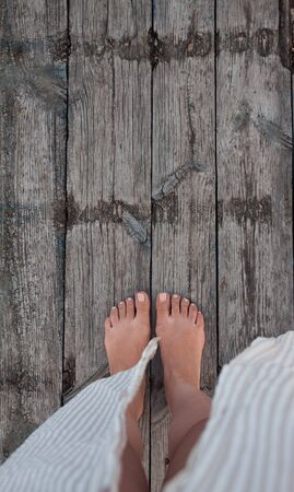 Beautiful female bare bare tanned legs with pink pedicure on wooden beach flooring. Top view, copy space.