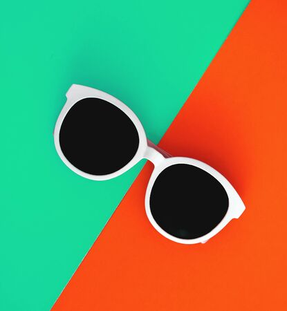 Sunny stylish white sunglasses on a bright blue-cyan and red-orange background, top view, isolated. Copy space. Flat lay.