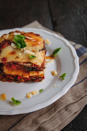 tradicional Parmigiana di melanzane: baked eggplant - italy, sicily cousine Baked eggplant with cheese, tomatoes and spices on a white plate. A dish of eggplant is on a wooden table Stockfoto