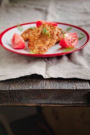 juicy meat-chicken chops and tomatoes on a white plate on a simple light linen background served with a fork and knife. Stockfoto