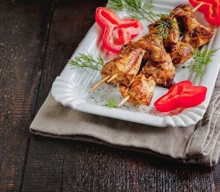 juicy meat-chicken skewers on wooden skewers on a white plate on a dark wooden background.