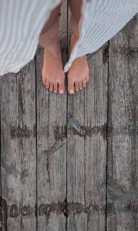 Beautiful female bare bare tanned legs with pink pedicure on wooden beach flooring. Top view, copy space. Standard-Bild - 129003648