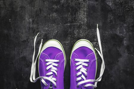 purple-pink-lilac sneakers with untied laces on a dark concrete background. Copy space. View from above