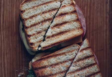 Two sandwiches on a wooden background, top view. Stack of panini with ham, cheese and lettuce sandwich on a cutting board.