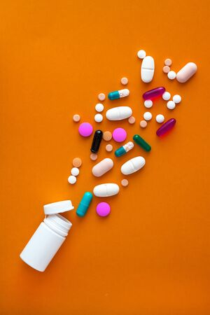 A variety of medicinal pills and pills poured out of the vial on a yellow background. Flat lay. Copy space. Trend. The concept of a healthy, bright, modern medicine and pharmacology Stock fotó - 129790374