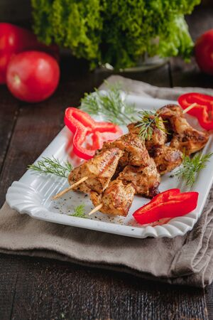 juicy meat-chicken skewers on wooden skewers on a white plate on a dark wooden background Фото со стока