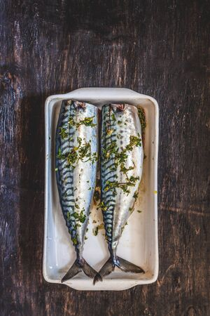 two raw fish mackerel in greens and herbs will be baked on a dark background. View from above. Retro effect Stok Fotoğraf